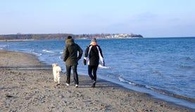 Gang door het overzees Jong paar met een hond op een zonnige de winterdag Royalty-vrije Stock Fotografie