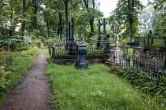 Gang door verlaten begraafplaats tussen graven en graven stock foto's