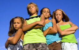 Gang of four serious kids. Over blue sky Stock Image