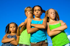 Gang of four serious kids. Group of four very serious kids over blue sky background Royalty Free Stock Photo