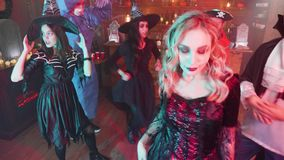 Gang of friends in scary costumes celebrates halloween in a bar decorated with holiday elements. Witch, vampire, pirate and evil physician dancing together stock video