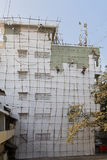 Gang of Indian barefoot Decorators. Painting exterior of a five story industrial building on a bamboo scaffold Stock Photos