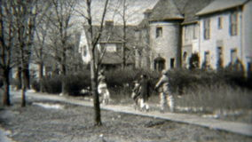 1938: Gang of kids rolling down the sidewalk together. ELYRIA, OHIO. Original vintage 8mm film home movie professionally cleaned and captured in 4k (3840x2160 stock video