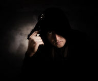 Gang member. Wearing a black hooded sweater holding a handgun in with an angry expression.Texture was added and also some grain is visible Stock Images
