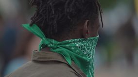 Gang member black man in green face mask walking around at crowded event. Gang member black man with dredlocks and green face mask walking around at outdoor stock video footage
