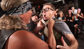 Gang Member Grabs Nerd. Nerd grabbed by collar in bar fight with tough gang member Stock Photos