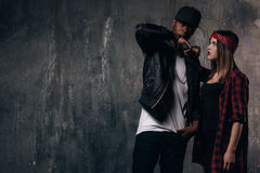 Gang members couple with gun. Criminal teenagers on dark background. Love and romance in outlaw family royalty free stock photography