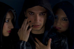Gang members in the darkness. Portrait of young gang members  dressed in black clothes wearing hood on their heads in the darkness with cigarette smoke around Stock Image