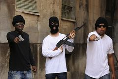 Gang members with guns and rifle. Gang members or guerrilla with gun and rifle on the street Stock Image