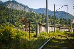 Gang op de spoorweg in de zomer, dwarsbalken die met gras worden overwoekerd royalty-vrije stock afbeelding