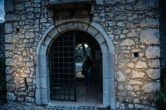 Gang op oude kasteeldeur met toeristenmeisje daarin royalty-vrije stock afbeeldingen