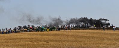 Gang plowing with five bottom plow. ROLLAG, MINNESOTA, Sept 2, 2017: Spectators observe a steam engine pull a five bottom gang plow in a wheat field at the Stock Images