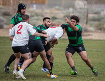 Gang Tackle. Colusa player gang tackle the ball carrier.  This match took place in Reno Nevada on April 11, 2014 between Colusa County Rugby Club (green) and Royalty Free Stock Photo