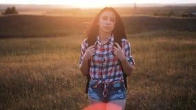 Gang van het Hipster de jonge meisje met rugzak die van zonsondergang op piekachtergedeelte genieten Toeristenreiziger op achterg stock videobeelden