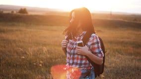 Gang van het Hipster de jonge meisje met rugzaksmartphone die van zonsondergang op piekachtergedeelte genieten Toeristenreiziger  stock videobeelden