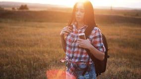 Gang van het Hipster de jonge meisje met rugzaksmartphone die van zonsondergang op piekachtergedeelte genieten Toeristenreiziger  stock video