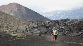 Gang van twee de jonge vrouwentoeristen onderaan de vulkaan na het beklimmen tot bovenkant stock videobeelden