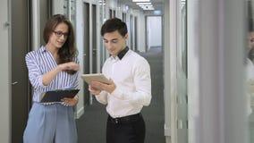 In gang verifiëren de bureauman met tablet en de vrouw met documenten gegevens stock footage