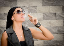 Gang woman smokes on the street, selective focus Royalty Free Stock Image