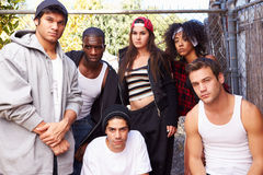 Gang Of Young People In Urban Setting Standing By Fence Stock Images