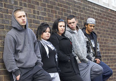 Gang Of Youths Leaning On Wall. Looking at camera stock photo