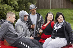 Gang Of Youths Sitting On Cars. Looking sidewards Stock Photos