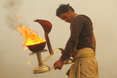Ganga Aarti in Varanasi. A priest at Dashashwamedh ghat performs daily Agni Pooja (Worship to Fire) wherein a dedication is made to Lord Shiva, River Ganga (the Stock Image