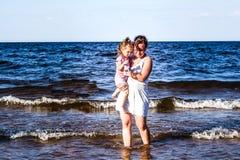 Gangdochter met haar moeder op de aard dichtbij het water stock afbeeldingen