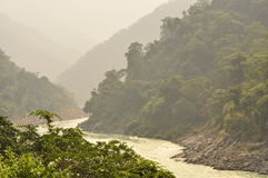 The Ganges, Indian sacred river in Rishikesh, India. The hindu sacred river Ganges among heavy forested hills near Rishikesh, India. Morning hazy summer light Stock Photography