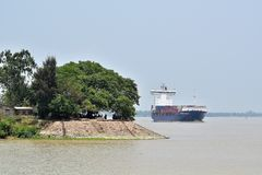 The Ganges at summer noon. An image of an idle summer noon over the Ganges at West Bengal, India, during tide hours. The cargo is heading to Kolkata port stock images
