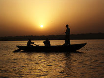 Ganges Sunset. Three men in a rowing boat on the ganges in varanasi, india Stock Photos