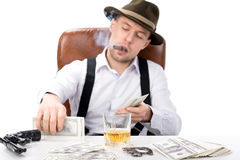 Gangster. Sitting at a table counting money. on the table gun and brass knuckles royalty free stock photo