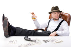 Gangster. Sitting at a table counting money. on the table gun and brass knuckles stock image