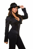 Gangster attire. Attractive long hair brunette woman wearing low cut black suit and black old gangster style fedora hat standing on white with serious expression stock photography