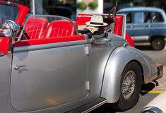Gangster car. Vintage cabrio car with gangster tools - tommy gun, hat and gloves Stock Images