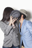 Gangster couple hiding behind a hat and kissing Stock Images