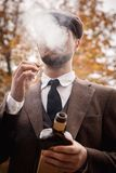 Gangster in a good suit smokes and holds a bottle of whiskey. Gangster in a good suit, a cap smokes and holds a cigarette and a bottle of whiskey Stock Photos