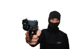 Gangster with a gun. Man wit a hood aiming a gun on a white isolated background Stock Photos