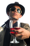Gangster with a gun offering a drinks. Isolated white background Royalty Free Stock Image