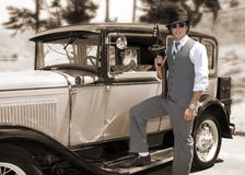 Gangster with gun and old car. A sepia view of a well-dressed gangster holding a tommy or machine gun and posing beside a vintage 1930 Model A touring car Royalty Free Stock Image