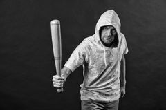 Gangster guy threaten with bat weapon. Man hold baseball bat, aggression. Hooligan wear hood in hoody, fashion. Aggression, anger. And violence concept, blaack royalty free stock photography