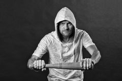 Gangster hold baseball bat. Hooligan wear hood in hoodie tshirt. Bearded man threaten with bat weapon. Aggression or. Anger and violence concept, black and royalty free stock photos