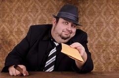 Gangster holding brown envelope Stock Photo