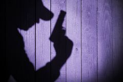 Gangster or investigator or spy silhouette on natural wooden wal Stock Image