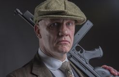 Gangster with a machine gun leaning on his shoulder. Portrait of a mature Victorian gangster with a machine gun leaning on his shoulder stock photo