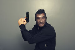 Gangster man with gun over grey Royalty Free Stock Photography