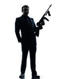Gangster man holding thompson machine gun silhouette Stock Photos
