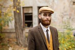 Gangster med ett skägg och hatt nära en övergiven byggnad retro utomhus fotografering för bildbyråer