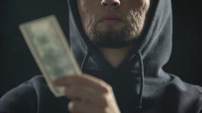 Gangster pericoloso che giudica soldi nella stanza scura pieni di fumo, pagamento per il crimine video d archivio