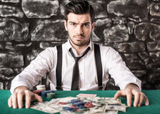 Gangster. Poker. View of young, confident, gangster man in shirt and suspenders, while he's playing poker game royalty free stock image